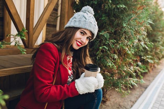 Porträt schönes junges mädchen mit langen haaren im roten mantel sitzen auf holztreppen im freien. sie hat eine graue strickmütze, weiße handschuhe, hält kaffee und lächelt.