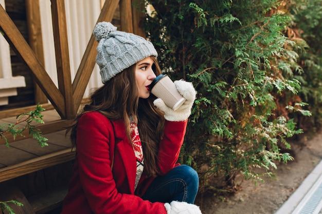 Porträt schönes mädchen mit langen haaren im roten mantel, strickmütze und weißen handschuhen sitzen auf holztreppen in der nähe von grünen zweigen im freien. sie trinkt kaffee und schaut zur seite.