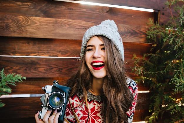Porträt schönes mädchen mit langen haaren in strickmütze, die spaß mit kamera auf holz haben.