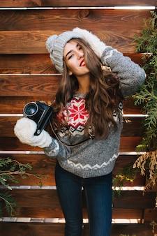 Porträt schönes mädchen mit langen haaren in strickmütze und handschuhen halten kamera auf holz. sie lächelt .