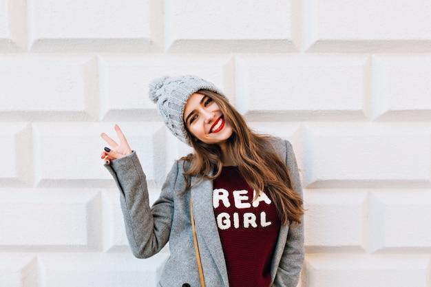 Porträt schönes mädchen mit langen haaren und roten lippen auf grauer wand. sie trägt einen grauen mantel und eine strickmütze. sie zeigt ein schild und lächelt.