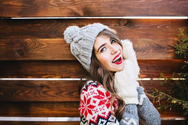 Porträt schönes mädchen mit langen haaren und roten lippen in strickmütze und handschuhen auf holz. sie lächelt .