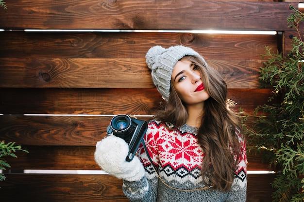Porträt schönes mädchen mit roten lippen in strickmütze und handschuhen, die kamera auf holz halten.