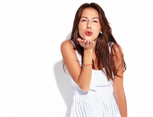 Porträt schönes niedliches brünettes frauenmodell im lässigen sommerkleid ohne make-up lokalisiert auf weiß. einen kuss geben