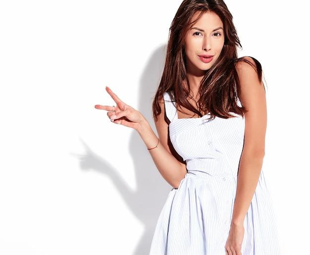 Porträt schönes niedliches brünettes frauenmodell im lässigen sommerkleid ohne make-up lokalisiert auf weiß. friedenszeichen zeigen
