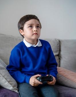 Porträt-schulkind, das videospiel oder spielekonsole hält