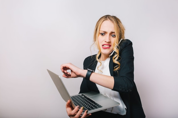 Porträt sehr beschäftigt junge geschäftsfrau im formellen anzug mit laptop, der am telefon spricht und auf uhr schaut. verspätung, arbeit, management, treffen, arbeiten, beruf