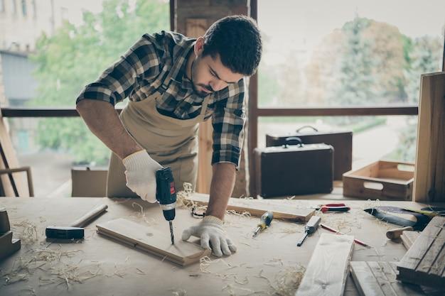 Porträt seines er netten attraktiven ernst fokussierten fleißigen erfahrenen kerls, der bohrer beim erstellen eines neuen hausbauprojekts bestellt, bestellen sie einen geschenkeladen im modernen industriellen loftstil