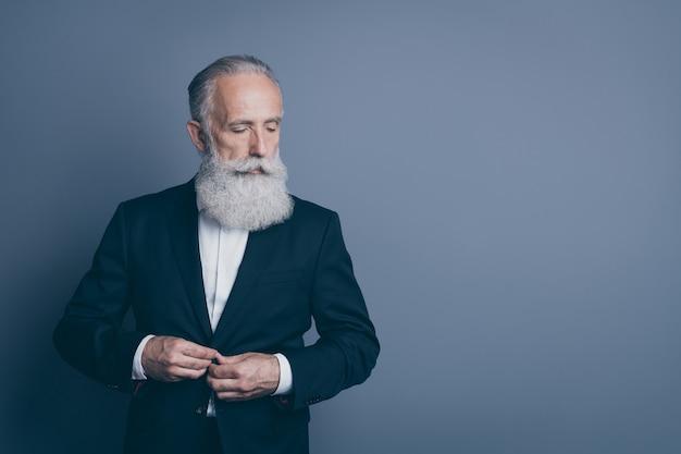 Porträt seines er schönen attraktiven schicken noblen ernsthaften inhaltsorientierten grauhaarigen mann macho, der smokingverschlussknopf bereitstellt, der über dunkelgrauem pastellfarbhintergrund lokal vorbereitet
