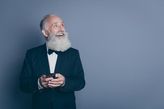 Porträt seines er schönen attraktiven schicken noblen fröhlichen fröhlichen fröhlichen grauhaarigen mannes, der smoking mit gerät verwendet, das neue idee beiseite schaut, die über dunkelgrauem pastellfarbenem hintergrund lokalisiert wird
