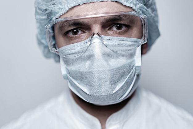 Porträt selbstbewusster arzt im schutzanzug mit gesichtsmaske und brille. konzept der corona-virus-quarantäne, covid-19