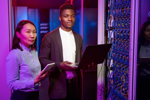 Porträt selbstbewusster multiethnischer it-ingenieure, die mit geräten im dunkelblauen serverraum stehen und mit supercomputern arbeiten