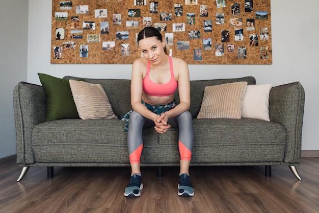 Porträt sportliche frau, die auf dem sofa sitzt, das aufwirft