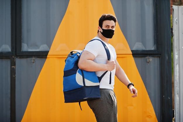 Porträt sportlicher arabischer mann in der schwarzen medizinischen gesichtsmaske mit rucksack, der gegen gelbes dreieck während der coronavirus-quarantäne gestellt wird.