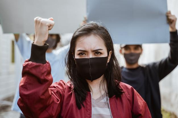 Porträt studentinnen demonstrieren mit ihren freunden, die leeres papier im hintergrund nach gesundheitsprotokollen halten