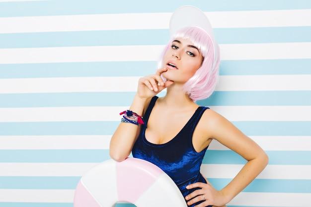 Porträt sylish sommer attraktives modell im blauen badeanzug mit geschnittener rosa frisur mit großem lutscher auf gestreifter blauweißer wand. junge sexy frau, erstaunliche, fröhliche stimmung, schauend.