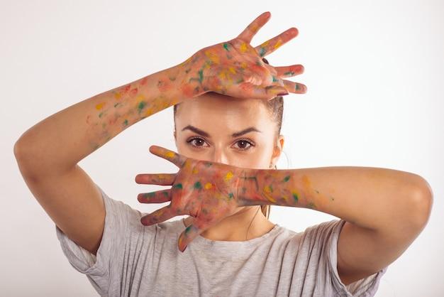 Porträt teenager-mädchen bedeckt ihr gesicht mit ihren handflächen in farbe auf weiß isoliert