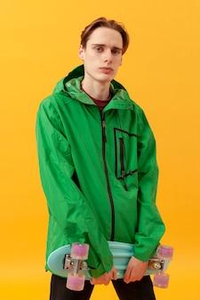 Porträt teenager mit grüner jacke und skateboard