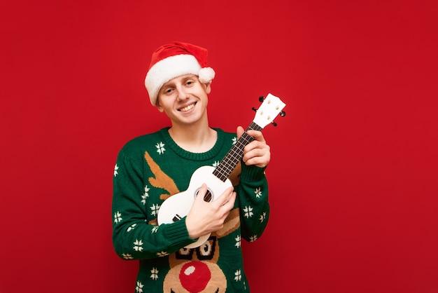 Porträt teenagerjunge mit weihnachtspullover mit ukulele