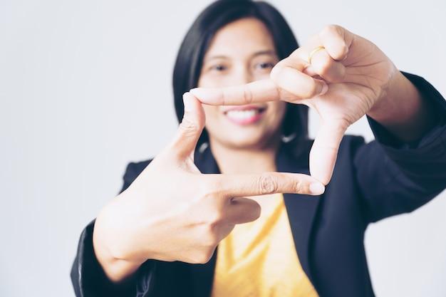 Porträt-überzeugte asiatische geschäftsfrau, die hand auf weiß darstellt