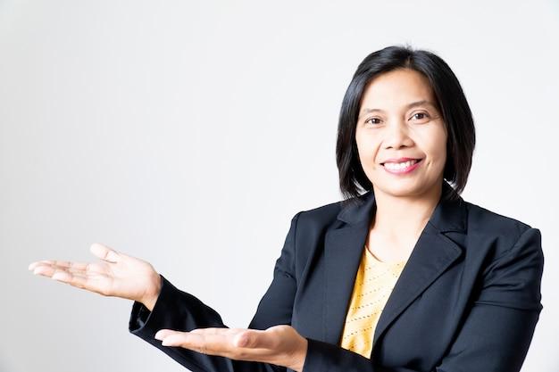 Porträt-überzeugte asiatische geschäftsfrau, die mit der hand auf weiß sich darstellt