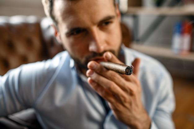 Porträt und nahaufnahme des jungen gutaussehenden geschäftsmannes in seinem eigenen büro. er raucht zigarre. guy sitzt mit zuversicht auf dem boden. konzentriert und kühl.