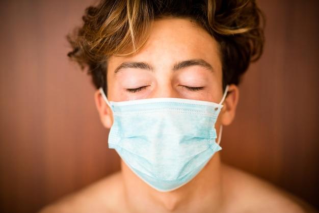 Porträt und nahaufnahme eines männlichen teenagers oder tausendjährigen jungen mit engen augen, die eine medizinische und chirurgische maske im gesicht tragen, um coronavirus oder covid-19 oder jede art von krankheit oder grippe zu verhindern