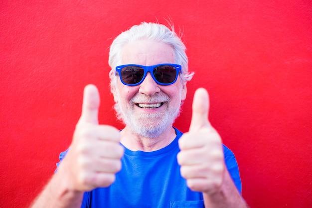 Porträt und nahaufnahme eines reifen und alten mannes, der eine blaue sonnenbrille trägt und in die kamera schaut - fröhlicher und glücklicher senior mit rotem hintergrund, der spaß hat und genießt
