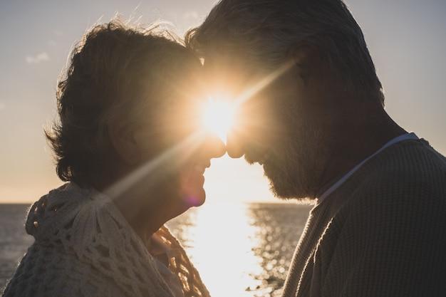 Porträt und nahaufnahme von zwei glücklich verliebten senioren, die sich lächelnd mit der sonne des sonnenuntergangs zwischen ihren köpfen ansehen