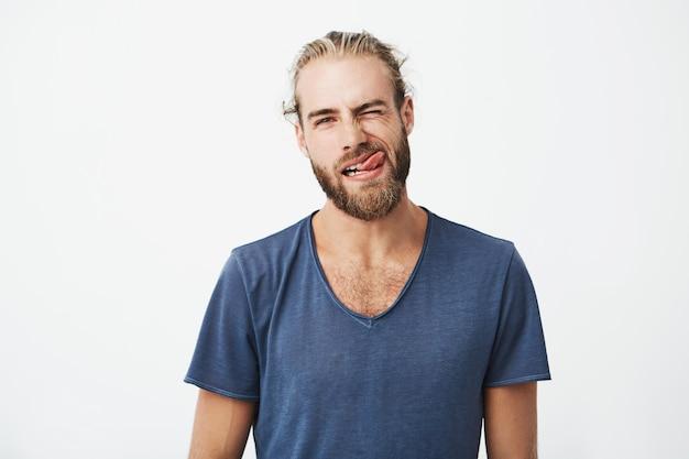 Porträt und schöner junger mann mit stilvollem haar und bart, die lustiges und albernes gesicht machen
