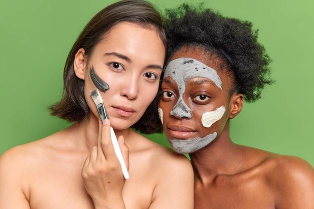 Porträt verschiedener junger frauen, die ernsthaft in die kamera schauen, tonmaske auftragen, kosmetischen pinselständer oben ohne verwenden