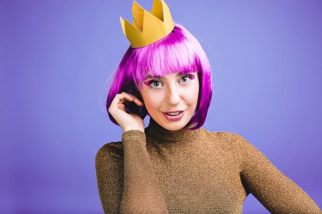Porträt verspielte junge frau mit geschnittenem lila haar, goldener krone, luxuskleid, das spaß hat. große feier, karneval, prinzessin stil, geburtstag, aufgeregt, positive emotionen.