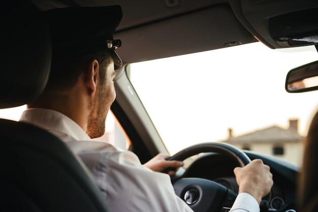 Porträt vom rücken des kaukasischen chauffeurmannes, der uniform und mütze trägt, rad hält und auto fährt