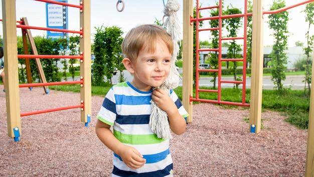 Porträt von 3 jahren, die auf dem spielplatz spielen und versuchen, auf das große seil im park zu klettern