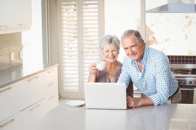 Porträt von älteren paaren mit laptop in der küche