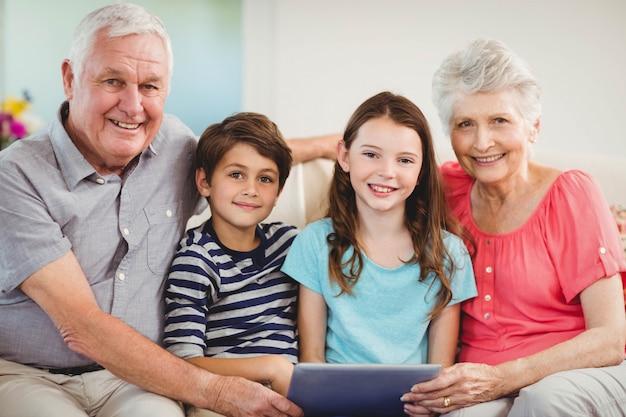 Porträt von älteren paaren und von ihren großartigen kindern, die digitale tablette im wohnzimmer verwenden