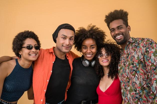 Porträt von afro-freunden, die spaß zusammen haben und gute zeit vor gelbem hintergrund genießen. freundschafts- und lifestyle-konzept.