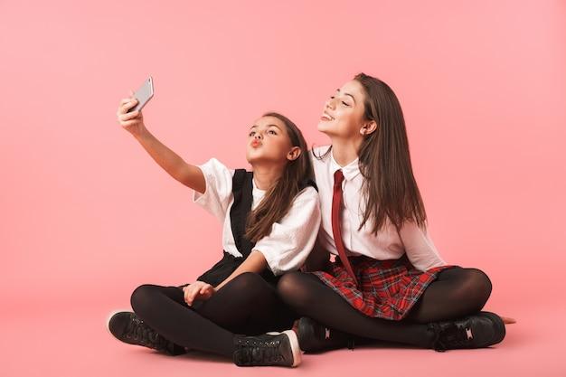 Porträt von amüsanten mädchen in der schuluniform unter verwendung von mobiltelefonen für selfie-fotos, während auf boden isoliert über roter wand sitzen