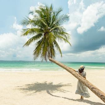 Porträt von asiatinnen fühlt sich an in der modischen weinlesekleidung glücklich, die kokosnussbäume steht
