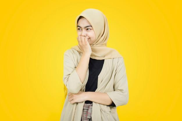 Porträt von asiatischen frauen beißt sich in die finger und schaut auf gelbe wand weg