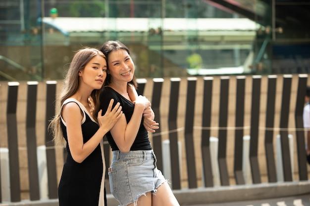 Porträt von asiatischen lgbtq+ lesbischen paaren der 20er und 40er jahre umarmen sich zusammen und lächeln glücklich. frau und transgender-frau macht es spaß, im freien zum einkaufen auf der straße zu gehen