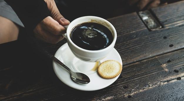 Porträt von asien mann mittleren alters, der die hand hält, um kaffee im café zu trinken.