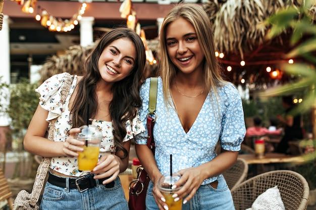 Porträt von attraktiven blonden und brünetten mädchen in stilvollen blumenblusen und jeanshosen, die weit lächeln und limonadengläser draußen halten