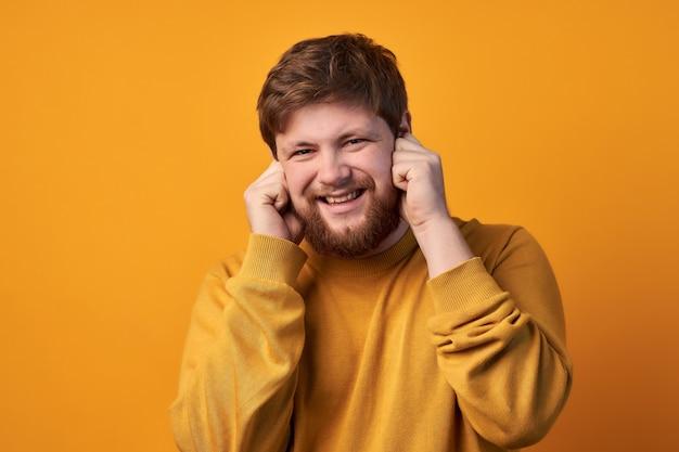 Porträt von attraktiven unrasierten männlichen pluggs ohren, wie nerviges geräusch hört, stirnrunzeln, zähne zusammenbeißt