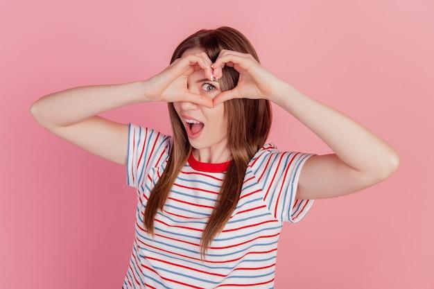 Porträt von aufgeregten lustigen süßen damenfingern zeigen herzzeichen-cover-auge auf rosa hintergrund