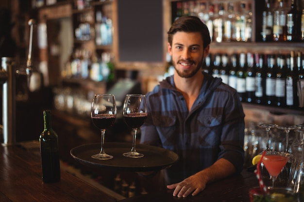 Porträt von barkeeper, der ein tablett mit gläsern rotwein hält