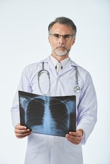 Porträt von berufsdoktor den bruströntgenstrahl halten geschossen und kamera betrachtend