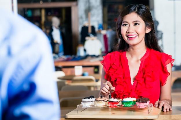 Porträt von bestellungskleinen kuchen einer netten asiatin in einer kühlen kaffeestube