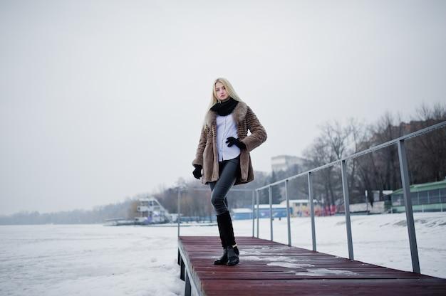 Porträt von blondinen der jungen eleganz in einem pelzmantel am pier, nebeliger fluss auf wintereis.