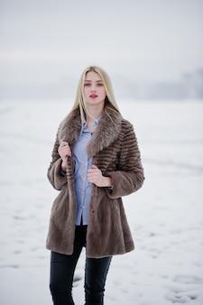 Porträt von blondinen der jungen eleganz in einem pelzmantel, nebeliger fluss auf wintereis.